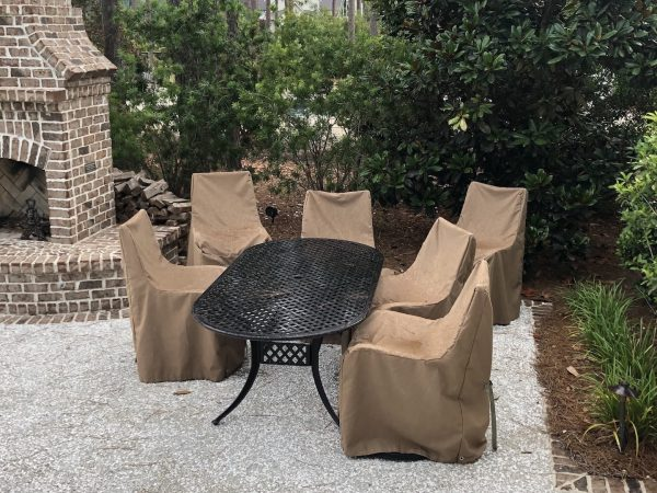 A set of metal patio chairs with custom GrillWraps covers on them to protect them from the weather.